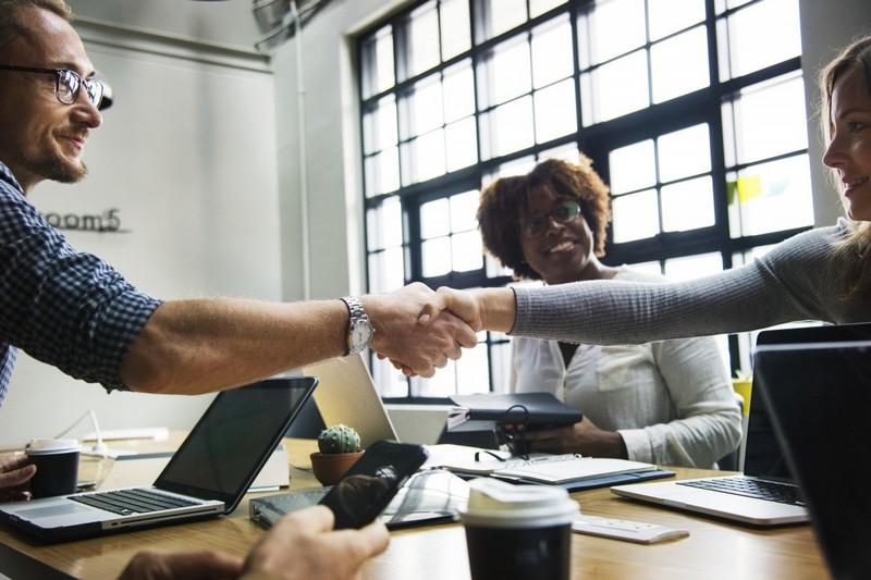Femme serre la main à un homme dans un bureau, en discutant de la notion de métiers féminins et masculins